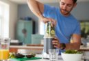 Man Making Healthy Juice Drink With Fresh Ingredients In Electric Juicer After Exercise