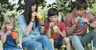 Young family relaxing outdoors drinking juice