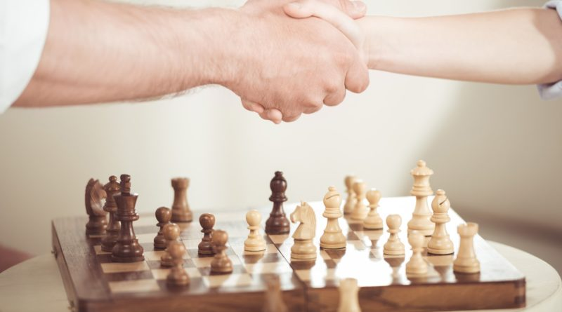 partial view of father and son shaking hands after playing chess board game
