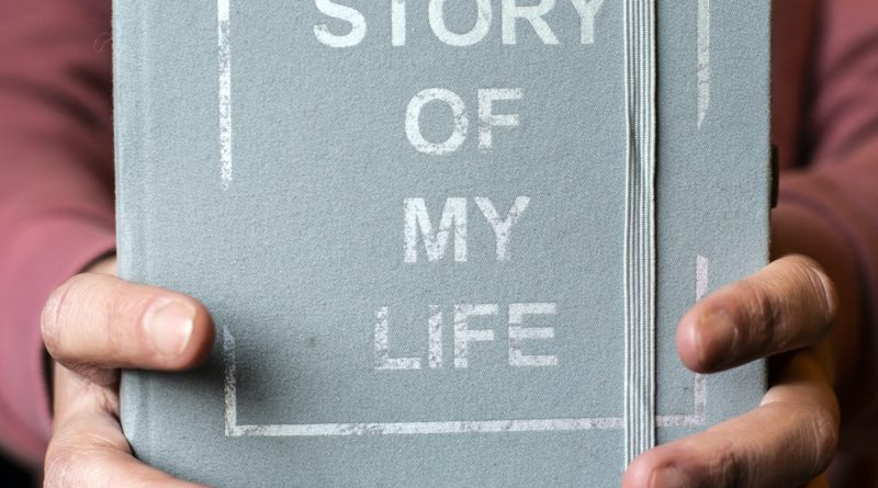 Woman hold notebook. Book notes for the Story of my life. Personal memoirs notes concept.
