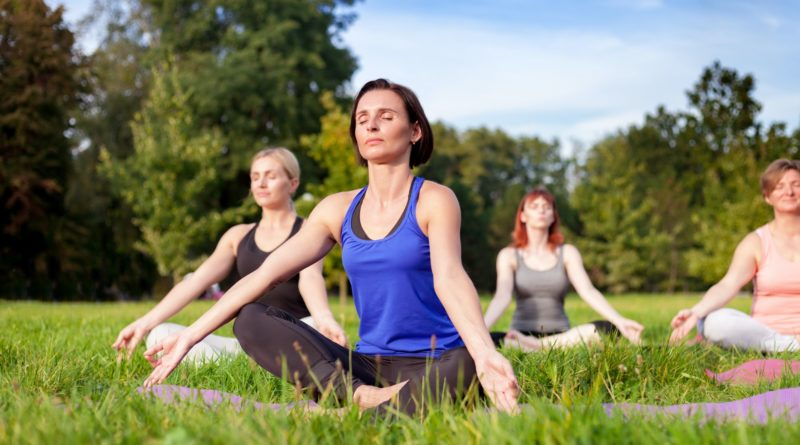 Yoga in the park, middle age woman doing exercises with group of mixed age people