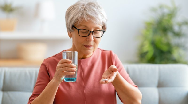 woman holding pill and glass of fresh water