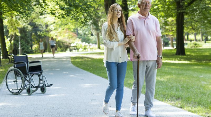 Woman helping elderly man with cane