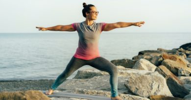 Young woman practicing yoga by the sea. Harmony and mental health concept.