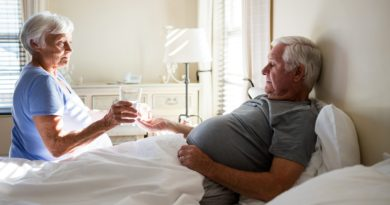 Senior woman giving medicine to senior man in the bedroom