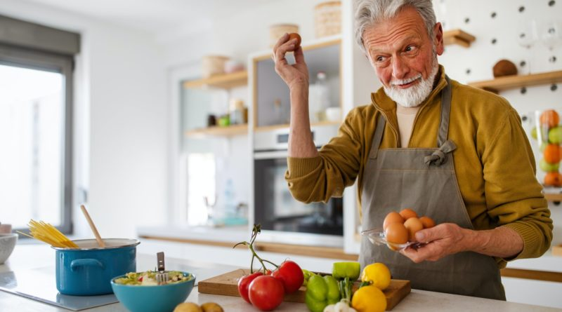 Happy retired senior man cooking in kitchen. Retirement, hobby people concept