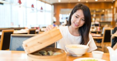 Woman open the bamboo steamer in chinese restaurant