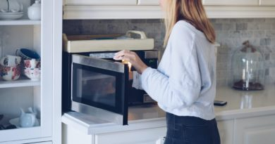 Young teenage girl is warming up food plate in a microwave oven
