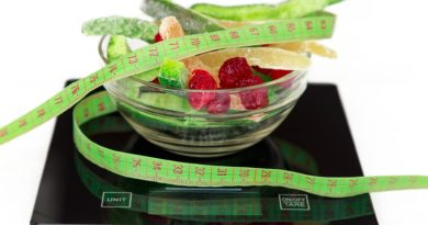 colored dried fruits in a transparent container stand on the kitchen scales